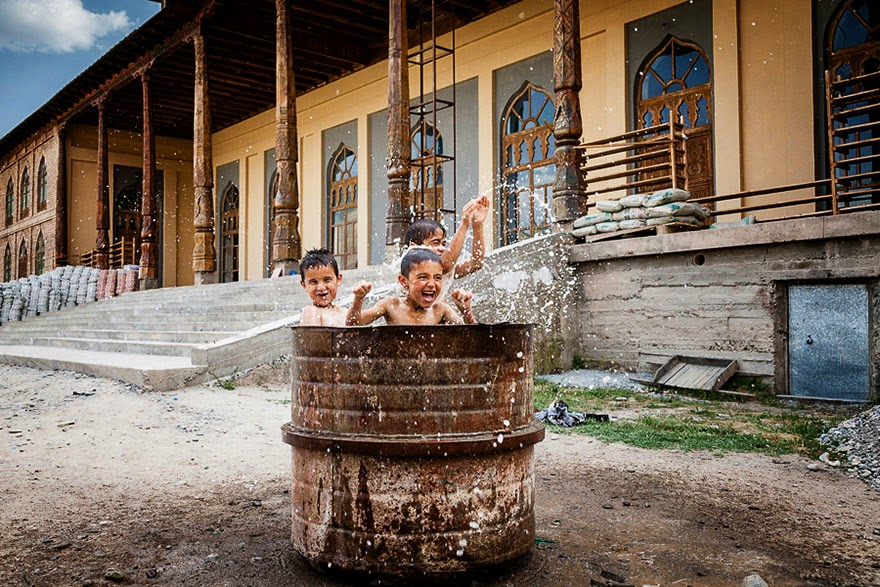 children playing in drum of water