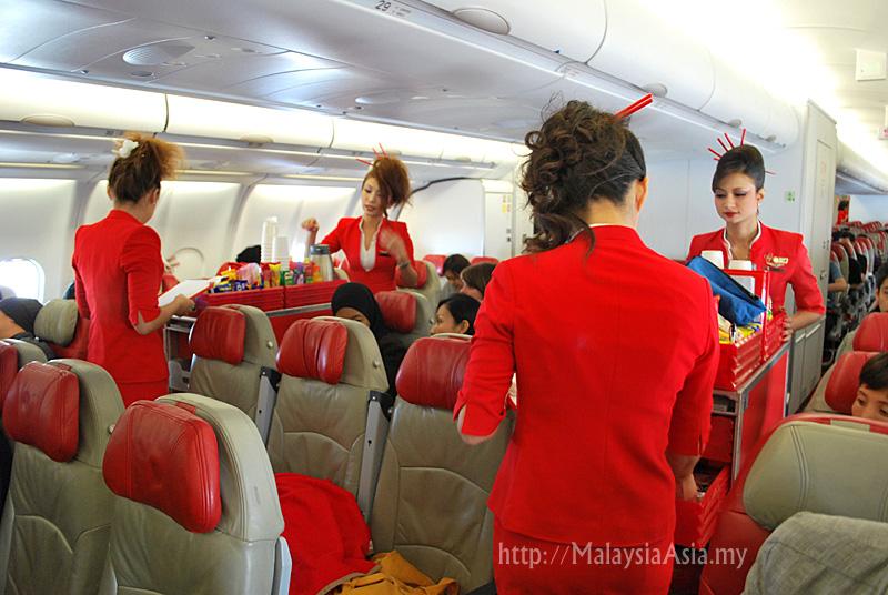 Air Asia X Flight Attendants serving in flight meals on the Osaka