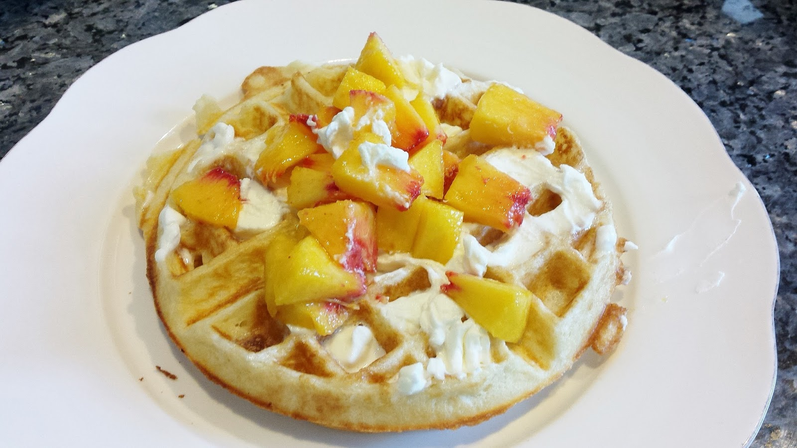 Waffle topped with whipped cream and fresh peaches