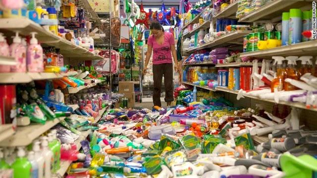 Nina Quidit membersihkan dolar Plus dan pihak pasokan toko pada tanggal 24 Agustus di American Canyon, California, setelah gempa mendatangkan malapetaka di rak-rak toko.