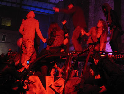 Party-goers swarm over a scrap car