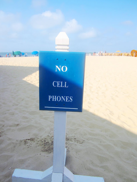 white sign post with blue sign on a beach