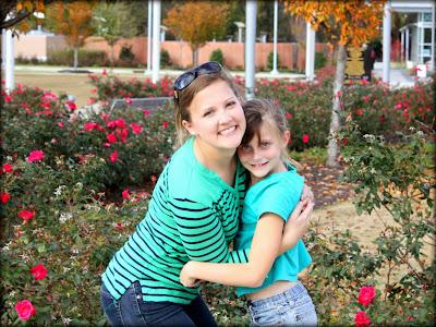 Allison and Caroline in front of rose bushes.