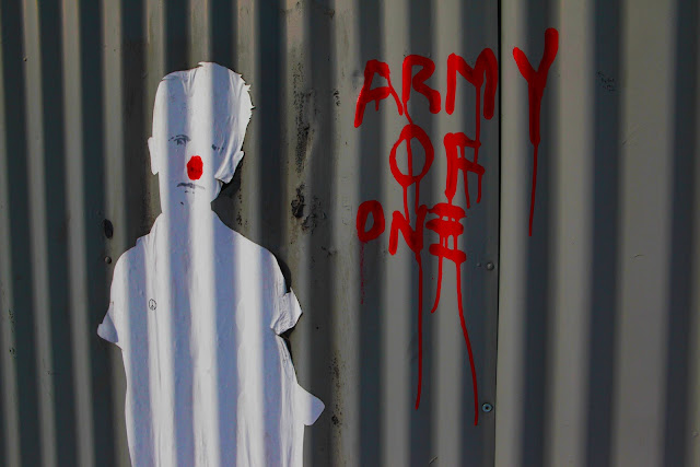New York City graffiti on a metal door that says 'Army Of One' next to a white boy with a red nose.