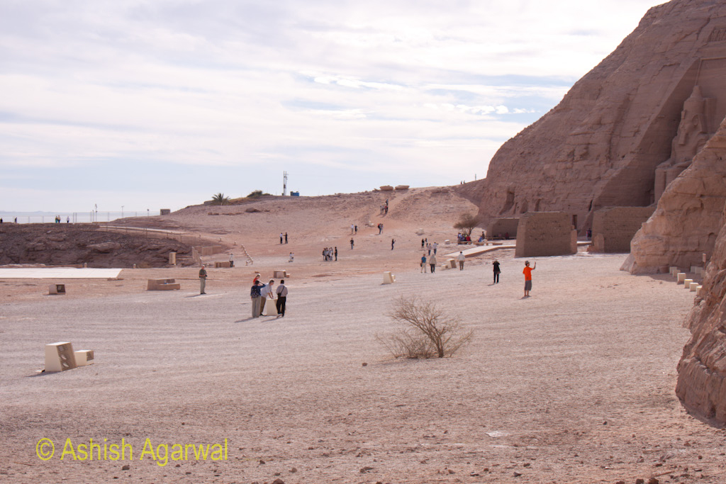 Side view of tourists in front of the statues and hillock of the Abu Simbel temple in Egypt