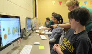 Teacher guiding students on computers