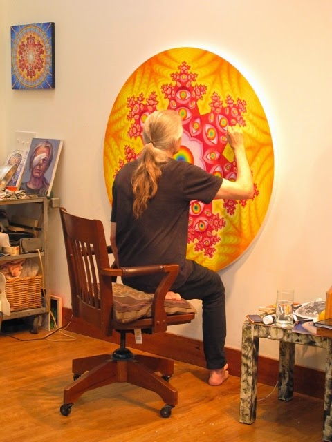 Alex Grey painting in his studio.