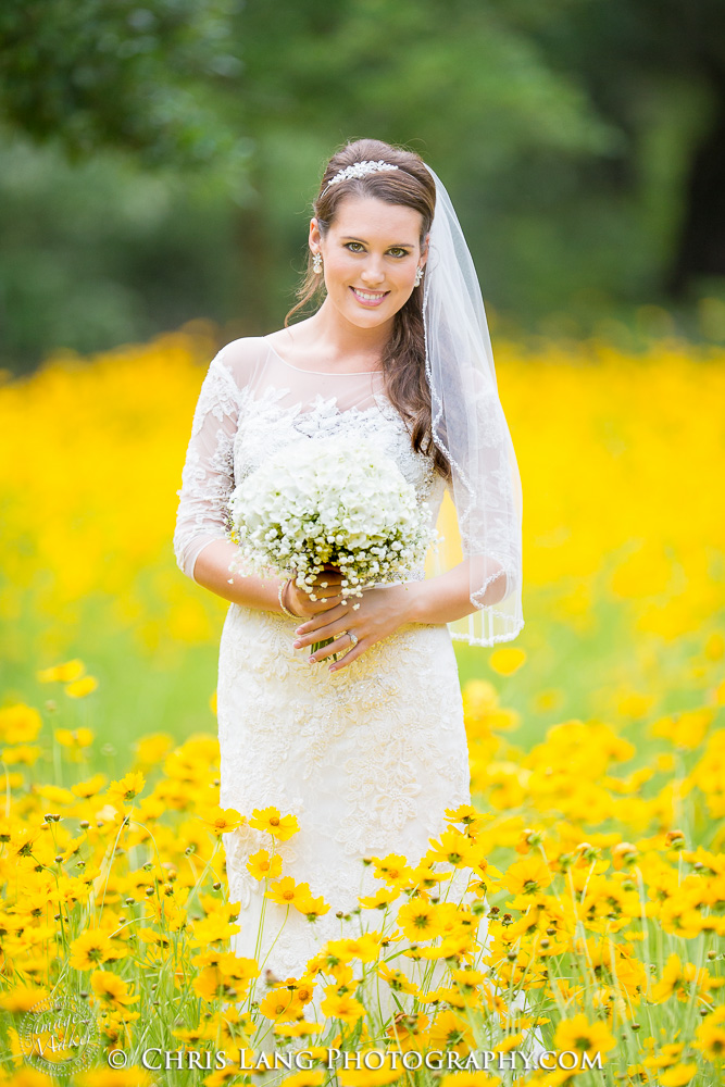 Beautiful  Bride holding wedding Bouquet  in a filed of yellow flowers  at Airlie Gardens in Wilmington NC
