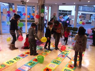 La imagen muestra a los niños y adultos de la fiesta jugando a la oca de la ONCE y saltando de casilla en casilla