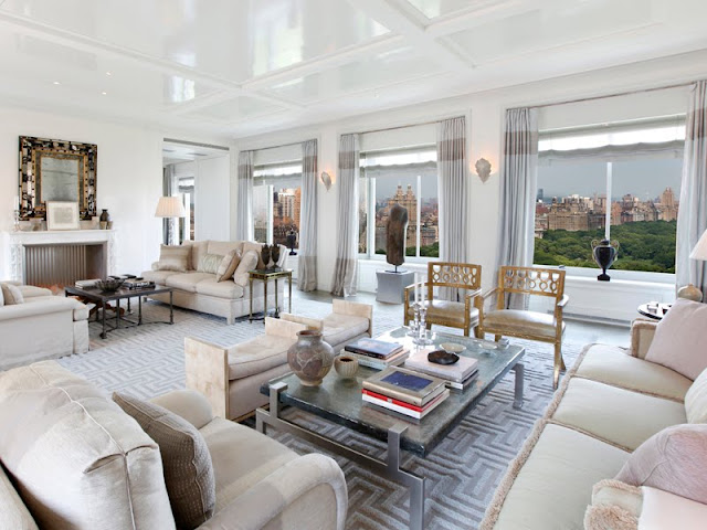 Alternative view of the living room showing it's many windows looking over Central Park, fireplace, and dueling sofas