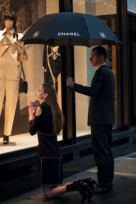 woman on her knees worships chanel. man holds an umbrella over her.