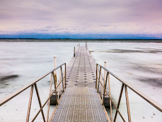 A winter time scenic of dock extending into frozen water at Thousand Islands National park Captured by Chris Gardiner Photography www.cgardiner.ca