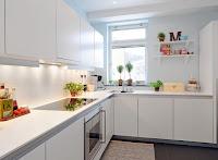 Decoracion de una cocina con muebles blancos y pequeñas plantas en macetas