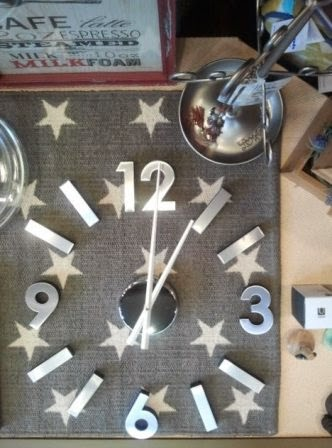 Reloj auto-adhesivo plateado sobre alfombra estrellas