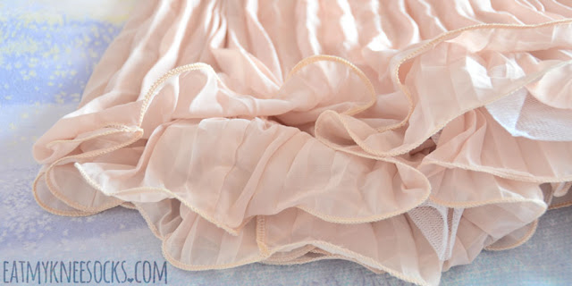 Close-up on the ruffled hem from SheIn, with four layers of flowy apricot-colored chiffon and white stiff mesh.