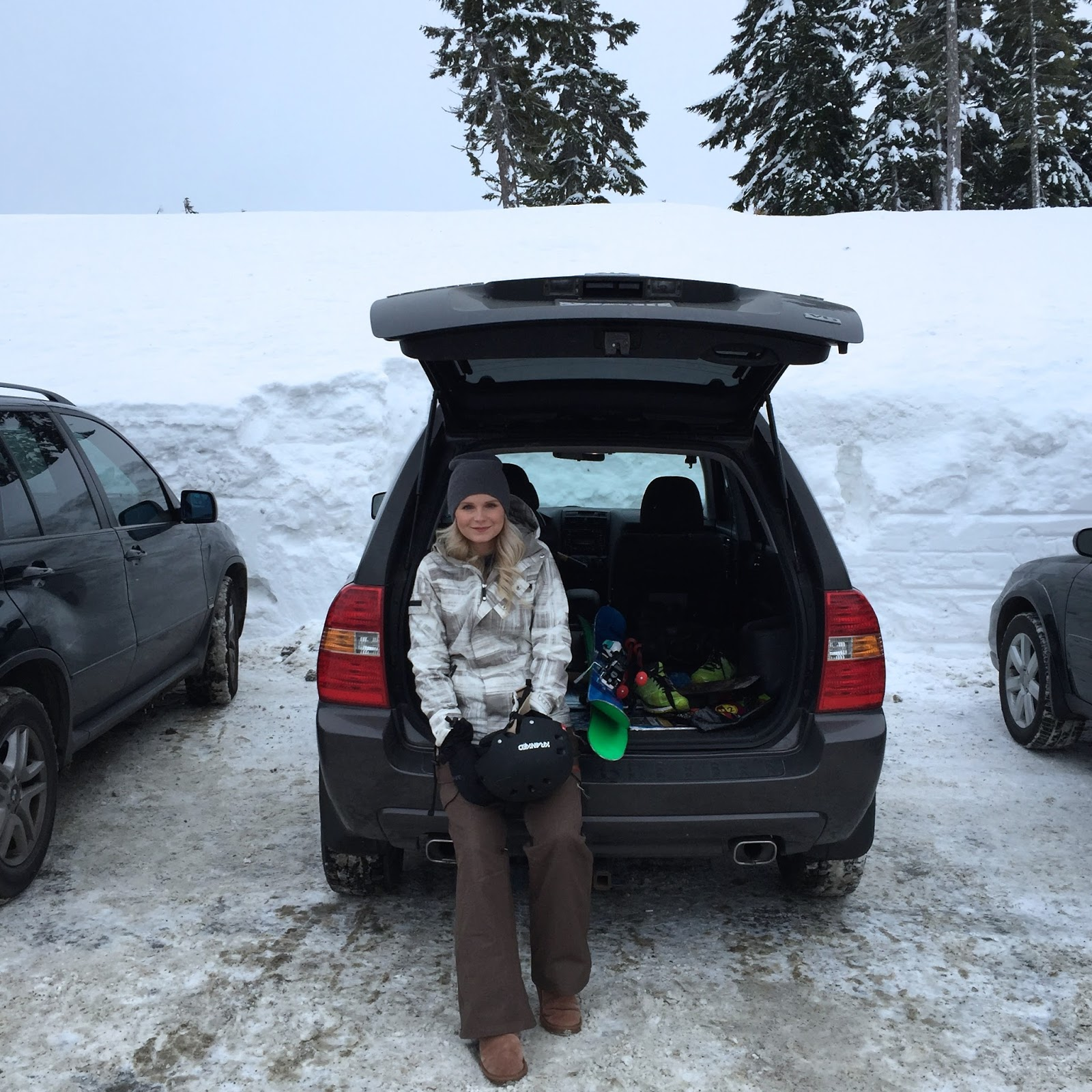a women sits on the bumper on the car, waiting to go  skiing