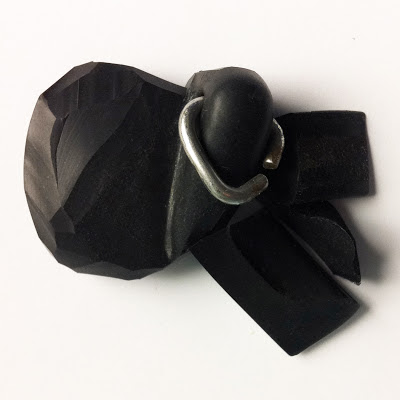A black sink plug that has been carved into an abstract shape.