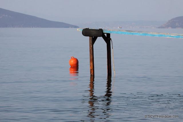 Skeletal pier and orange buoy in calm sea