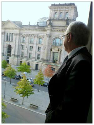 Ein Mann im Anzug und mit grauen Schläfen blickt aus einem höheren Stockwerk des Abgeordnetenhauses auf den Reichstag.