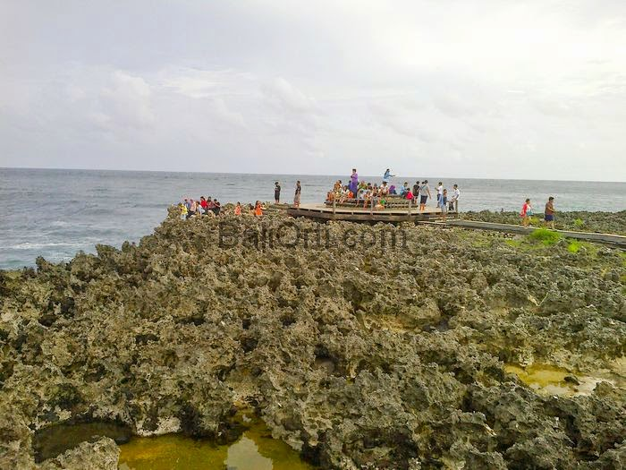 People are sitting waiting for the effects of water blow on the west side of Nusa Dua Beach , Bali Indonesia .