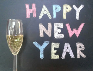 happy new year sign in colored chalk with champagne glass