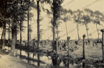 Photograph of a military encampment near a stream, captioned: View near the huts, Belgium, 1915 (D/DLI 7/424/2(72))