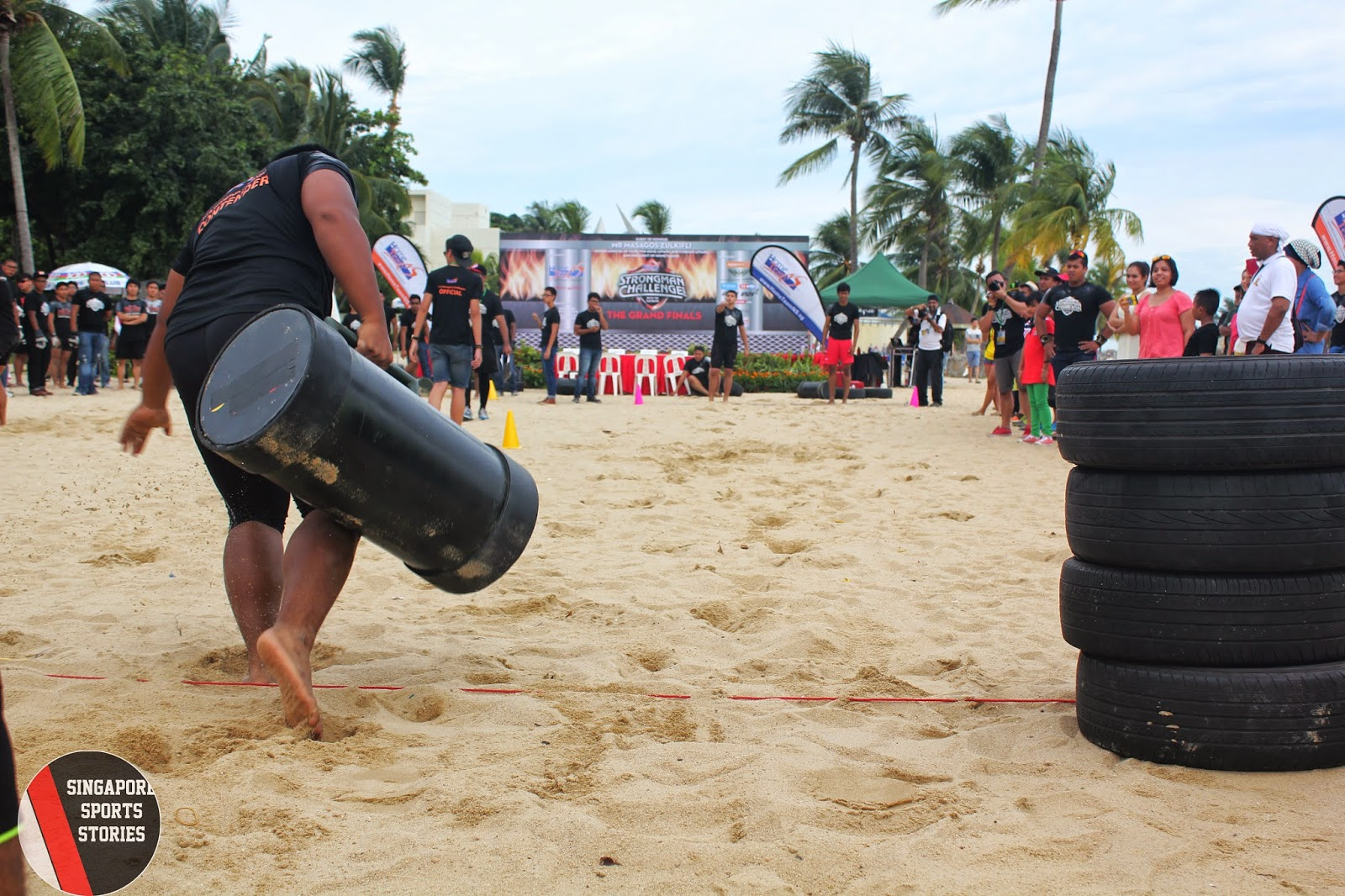A strongman hauling a 50kg log at HomeTeamNS Strongman Challenge 2014 as part of the team challenge