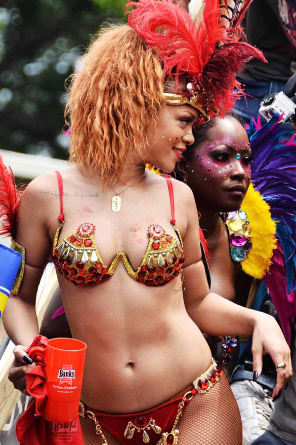 Rihanna climbed on board a float dressed in a cut away bra top and a pair of tiny red pants as she celebrated Kadooment Day.
