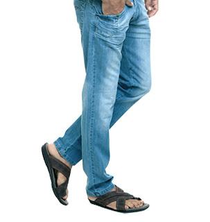 Homem usando jeans e chinelo slide de couro com tiras cruzadas - pés masculinos