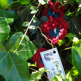 "Crocheted pansies nestled among shrubbery, bearing tag: ""Yarn Bombing @ Your Library"""