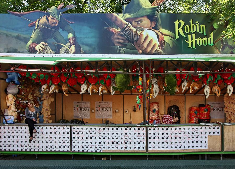 Barraca de tiro ao alvo, com diversos objectos suspensos e um painel do Robin Hood, na parte do telhado