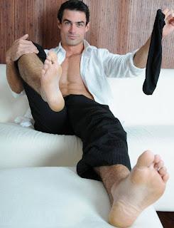 Homem retirando a meia e mostrando a sola do pé