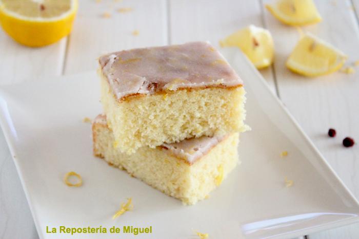 Foto frontal de dos trozos de brownie uno encima del otro sobre plato blanco llano cuadrado con rayaduras sobre la mesa y plato y limones partidos sobre la mesa.