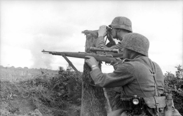 A German sniper (carrying Kar98k with 4x Zeiss ZF42 telescopic sight) and a spotter at Voronezh, Russia, 1942