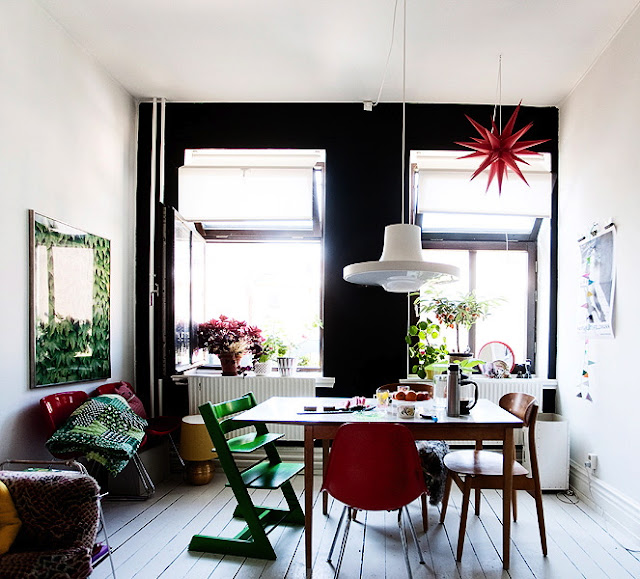 Sweden Swedish dining room black painted feature wall white pendant light table chairs red green white wood floors
