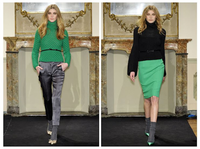 Two models from Les Copains' Fall 2011 Ready to Wear show. The model on the left is wearing a green sweater with a small belt at the waist and grey satin pants. The model on the right is wearing a black turtleneck sweater with a green skirt, green heels with grey socks