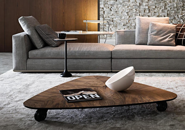 dark brown wooden triangle coffee table in the living room area rug with the simple item on top