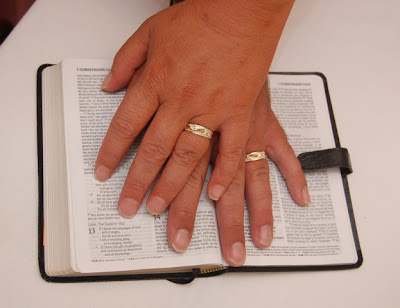 hands with wedding rings on the bible opened to 1 Corinthians 13