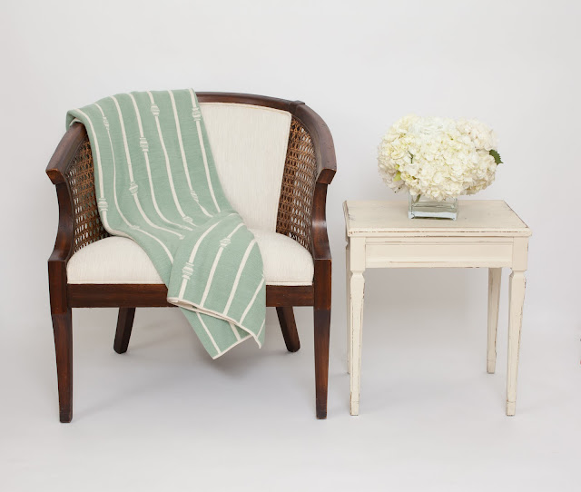 Nbaynadamas throw elegantly placed on on upholstered wood chair next to a white vintage side table holding a glass vase of white hydrangeas