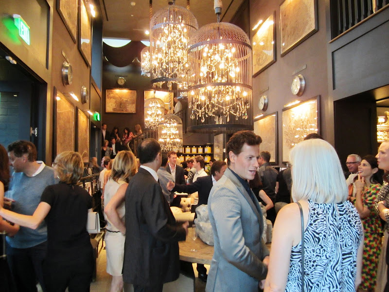 People mingling at the new Restoration hardware in a room with dark wood walls and birdcage chandeliers