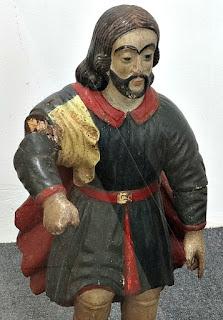 Santo Isidro, no Museu Missioneiro de São Borja. Figura masculina, com cabelos longos bipartidos e braços articulados. Escultura em madeira policromada.