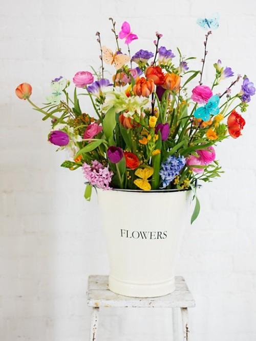 flores lindas em balde de metal sobre banco de madeira shabby chic