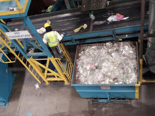 worker sorting plastic on conveyer belt