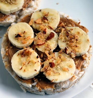 Peanut butter, honey, and banana rice cakes with toasted sesame seeds and crushed almonds