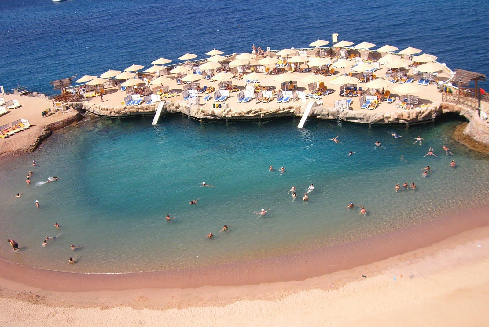 praia com águas cristalinas cercada de areias brancas e barracas