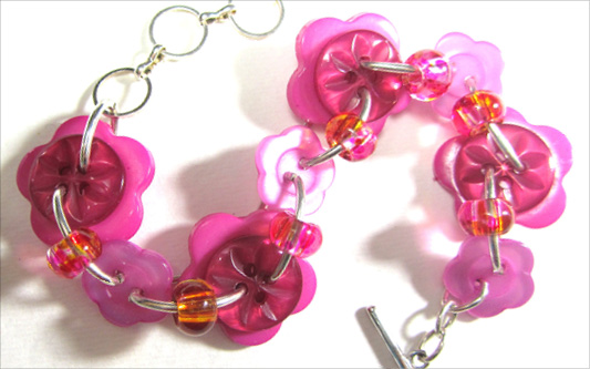 Cute bracelet has big flower buttons with carved flower buttons and glass accent beads