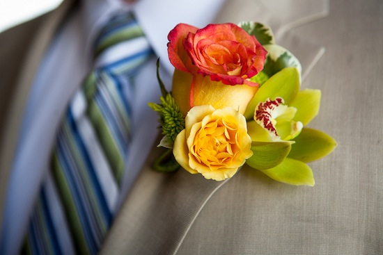bright orange, green and yellow boutonniere on the groom