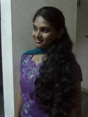 Homely looking Tamil girl showing off her long hair.