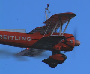 Model Breitling Stearman in flight with its nav light and smoke