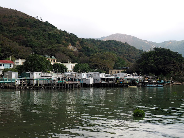 View of row of stilt houses in the distance, by the ocean at Tai O fishing village, Lantau Island, Hong Kong